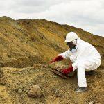 Aurora Environmental staff member sampling asbestos and soil at a contaminated site.